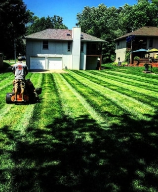 A Pro Mow employee mowing a lawn. The grass is green and shows striping.