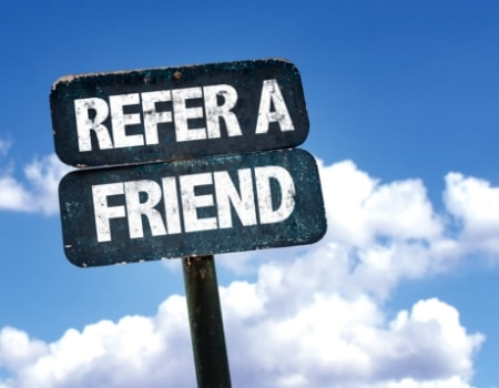 "A black sign reading, ""refer a friend,"" in front of a blue sky."