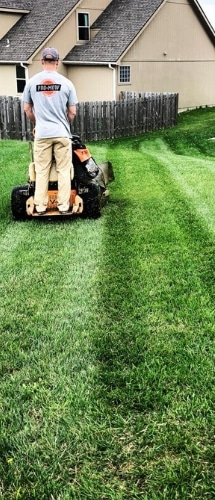 A Pro Mow employee in the process of mowing a lawn.